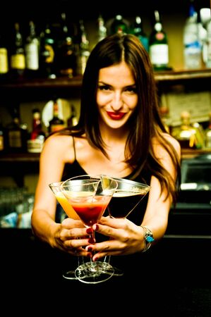 lounge bar: A young female bartender, photographed at work. Stock Photo