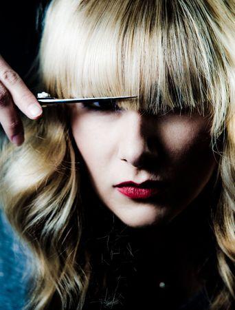 own: A hair stylist cutting her own hair, portrait.