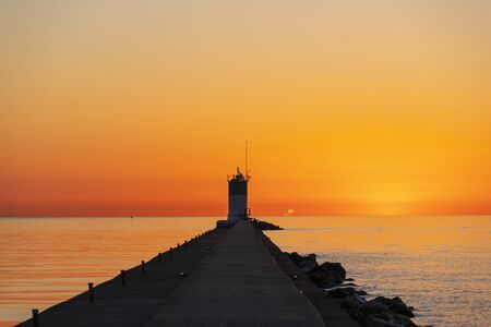 Sunrise over Lake Michigan lighthouse walkway