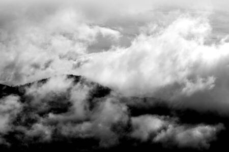 Clouds over mountain ranges with tress Foto de archivo