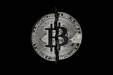 Bitcoin crypto currency coin in isolated black background cut in half. Foto de archivo