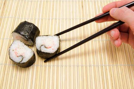 tekka: chopsticks in hand and sushi on bamboo tray Stock Photo