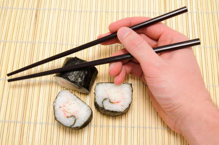 chopsticks in hand and sushi on bamboo tray photo