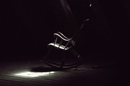 attic: lit old rocking chair in the attic Stock Photo