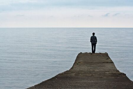 tonight: Man standing on the edge of the pier on the sea background Stock Photo