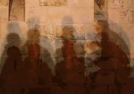 conversing: Four men conversing in the shade of stone wall background
