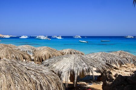 the furlough: Seascape with straw umbrellas and yachts. Tourism in Egypt, May 2012. Editorial