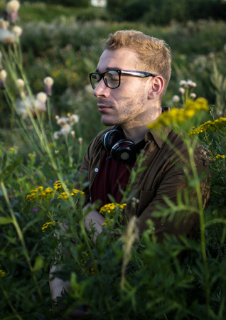 A single man with headphones and wearing glasses in a green field with flowers.