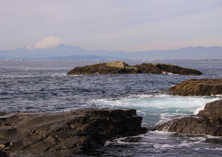 landscape with the Pacific Ocean, rocks and Mount Fujiyama on background. Nature of Japan.