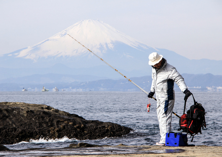 Fisherman on the rocks in the Pacific Ocean on Mount Fuji background. Nature of Japan. Kamakura, Japan