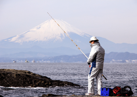 Fisherman on the rocks in the Pacific Ocean on Mount Fuji background. Nature of Japan. Kamakura, Japan, 01062013. Editorial