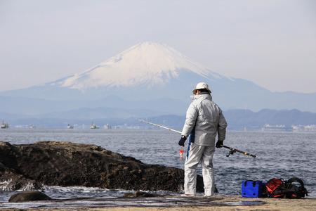 Fisherman on the rocks in the Pacific ocean on Mount Fuji background. Nature of Japan. Kamakura, Japan, 01062013. Фото со стока
