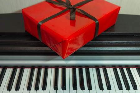 Big red present box on the piano. Christmas decoration of Interior. Happy birthday to you.