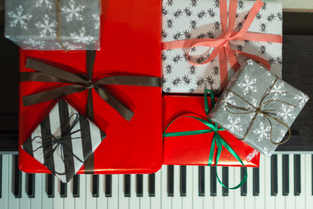 Colorful present boxes on the piano. Christmas holidays decoration of Interior.