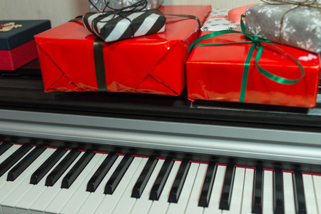 Colorful present boxes on the piano. Christmas decoration of Interior.