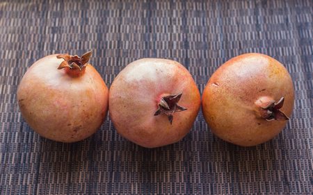 Three appetizing pomegranates on a brown background. Healthy fruits close up.