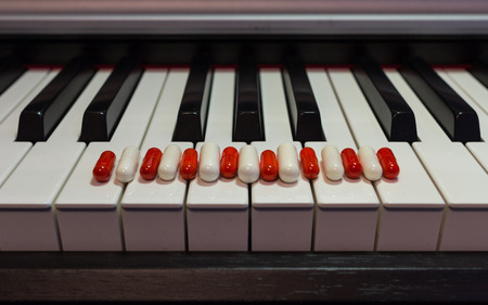 Pills on the piano keyboard. Concept of music and health. Stock Photo