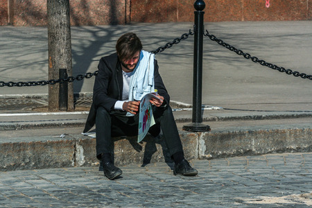 2010.04.11, Moscow, Russia. A man reading news paper sitting on the Red square. Tourists walking around Moscow.