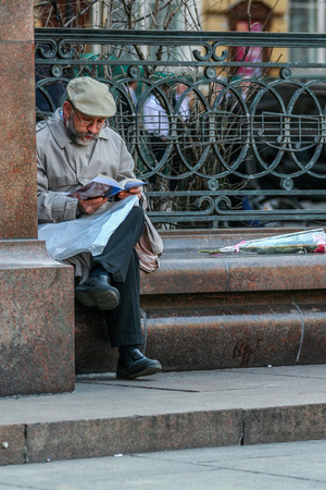 2010.04.11, Moscow, Russia. An old man reading news paper by the monument.