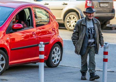 2010.04.11, Moscow, Russia. Homeless man walking down the street on red background.