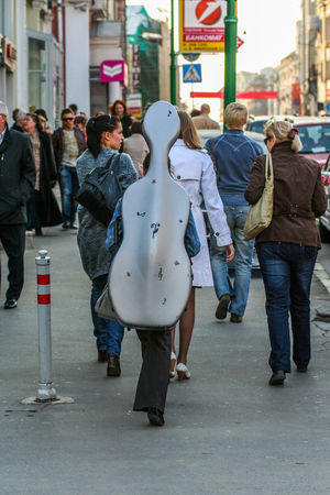 2010.04.11, Moscow, Russia. A girl musician carries a cello in a case on the back.