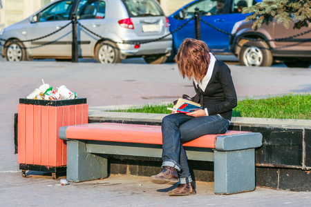 2010.04.11, Moscow, Russia. A young woman reading a book and sitting on the bench.