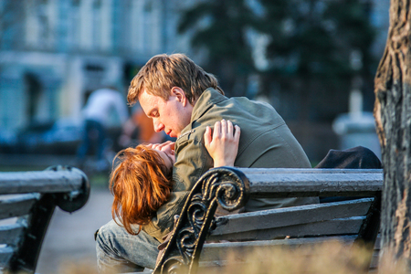 2010.04.11, Moscow, Russia. Couple in love sitting in the park Romantic kiss of young lovers. Editorial