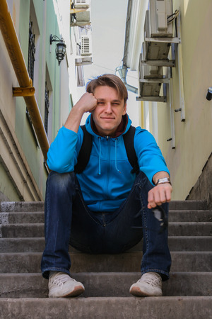 2010.04.11, Moscow, Russia. A young smiling man sitting on the stairs.