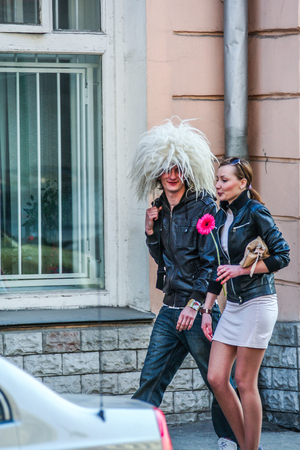 2010.04.11, Moscow, Russia. A young man wearing a woolen hat and a young girl walking down the street.