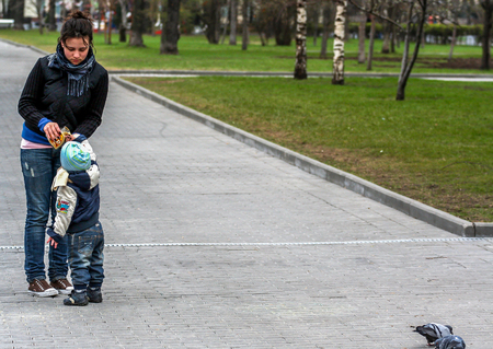 2010.04.18, Moscow, Russia. A little smiling boy catching pigeon. Young woman and her son walking in the park.