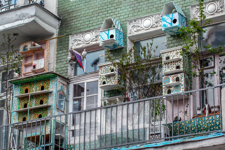 2010.04.18, Moscow, Russia. Colorful bird houses on the balcony. Pigeons living on the balcony. Editorial