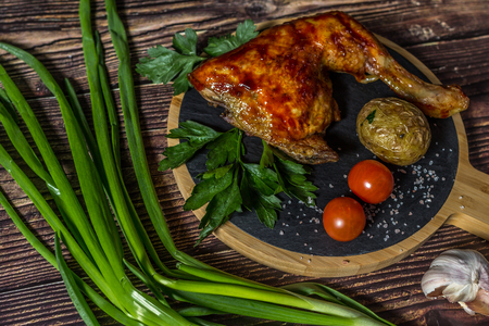 Grilled chicken, potatoes, tomatoes, salad, green onion and salt. Grilled food on wooden background.