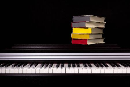 stack of colored books on a black background. Concept of education and reading. Stock Photo