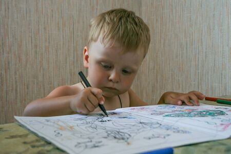 Little boy sitting by the table and playing coloring book. Young artist working at child room. Stock Photo