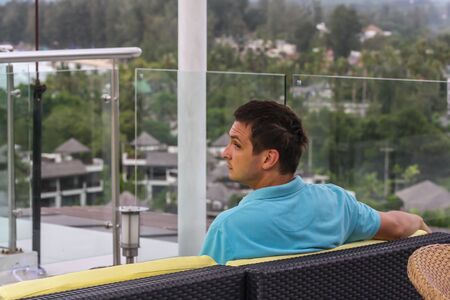 A young man sitting on the sofa on the roof of the hotel, back side view. Tourism on Phuket. Banco de Imagens