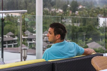 A young man sitting on the sofa on the roof of the hotel, back side view. Tourism on Phuket.