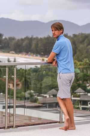 A young man standing by glass fence on the roof of hotel. A guy looking to camera on background of Phuket beach. Banco de Imagens
