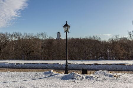 Winter landscape of the road, church and street lamp on background of blue sky. Banco de Imagens