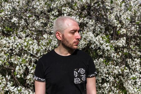 2019/05/08, Moscow, Russia. A young bearded man walking around Kolomenskoye park. Portrait of an young blonde guy in profile standing by flowering tree. Imagens