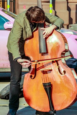 2015.04.12, Moscow, Russia. Street musicians at spring day. young man playing double bass on pedestrian street.
