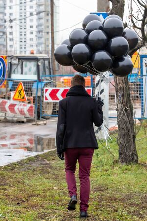 2015.11.22, Moscow, Russia. birthday is a sad holiday concept. A young blonde man wearing black scarf and coat holding black balloons going down street, back side view.