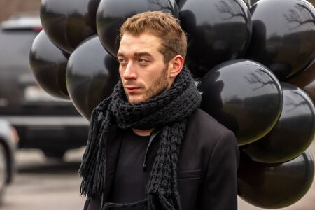 birthday is a sad holiday concept. A young blonde man wearing black scarf and coat holding black balloons standing on the street.