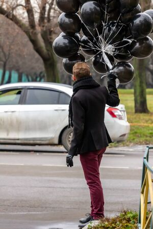 2015.11.22, Moscow, Russia. birthday is a sad holiday concept. A young blonde man wearing black scarf and coat guy holding black balloons and smoking.
