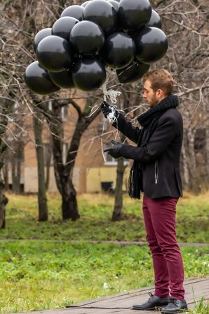 2015.11.22, Moscow, Russia. birthday is a sad holiday concept. A young blonde man wearing black scarf and coat holding black balloons standing on background of apple trees garden.