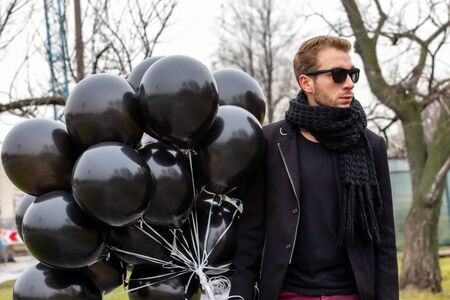A young blonde man wearing sunglasses and black scarf holding black balloons, side view. Banque d'images