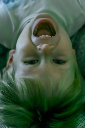 portrait of a little fair-haired cheerful boy lying upside down.