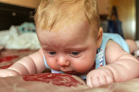 newborn boy lies on his stomach on the bed and looking down. baby boy in the early days of home. Reklamní fotografie