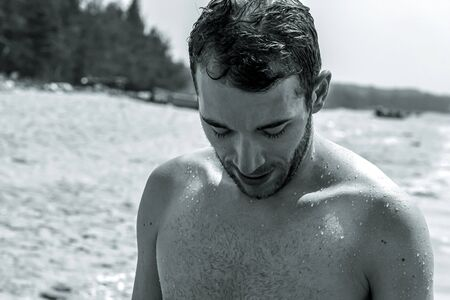 black and white photo of a young handsome bearded man who had just stepped out of the sea to the beach