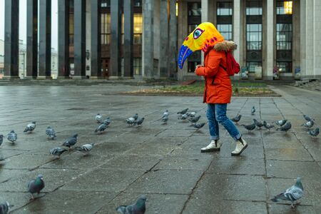 A young woman wearing red jacket and a mask (bird's head) having fun on the square by the Russian state library.
