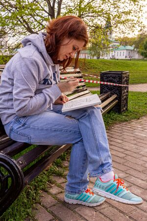 A young woman drawing a picture with watercolor paints, sitting on the bench. drawing on the open air.